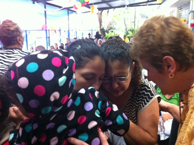 Minister Janis Watkins prays for a new believer as she excepts Christ.